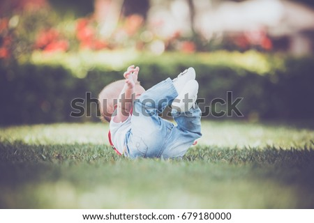 Baby boy falling on the grass