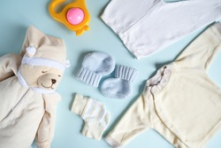 Baby boy goods on blue background. Kit of clothes and toys for infant. Top view. Infancy concept.
