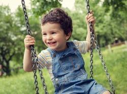 Baby boy having fun on a swing.