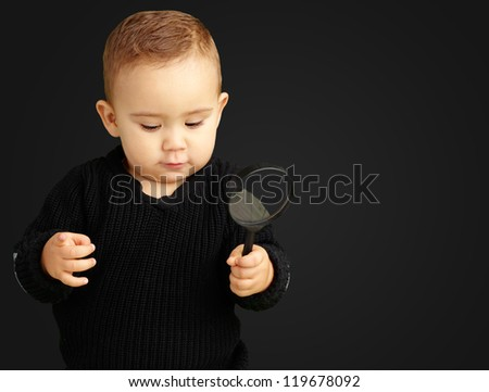 Baby Boy holding a magnifying glass against a black background