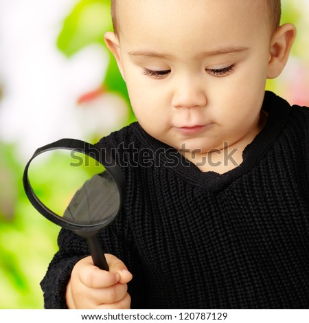 Baby Boy holding a magnifying glass against a nature background