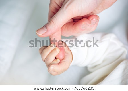Baby boy holding mother's hand, squeezes the fingers. The concept of empathy, trust, care and tenderness of motherhood #785966233