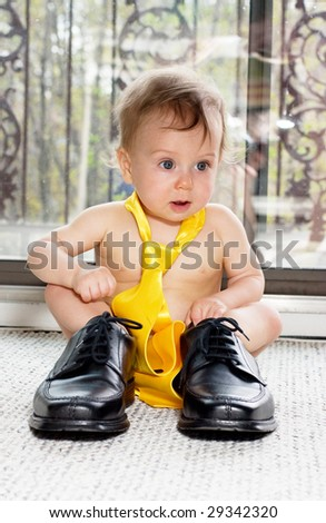 Baby boy in adult shoes and a tie