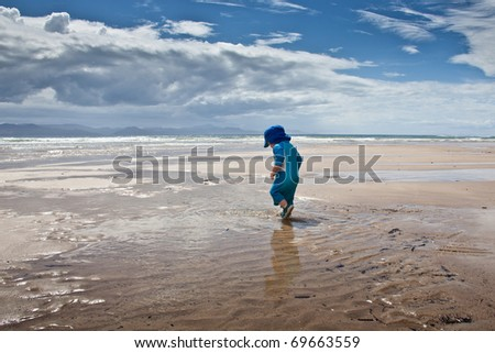Baby boy in blue sunsuit walking on large beach