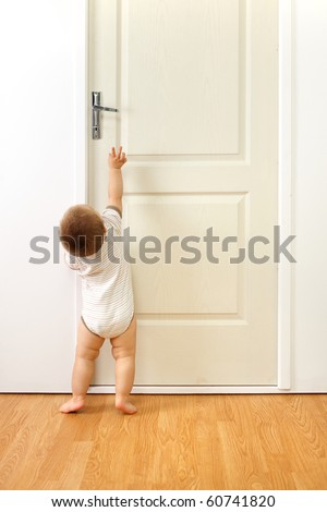 Baby boy in front of a closed door, trying to reach the handle