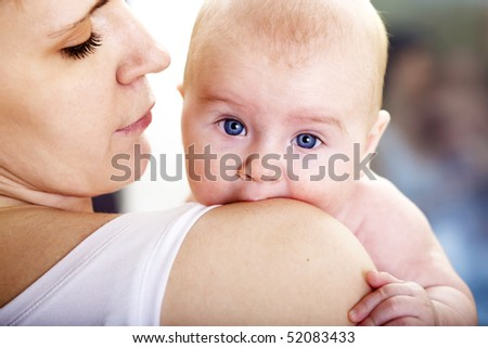 baby boy in mothers arm looking with surprise; shallow DOF, focus on baby's eyes