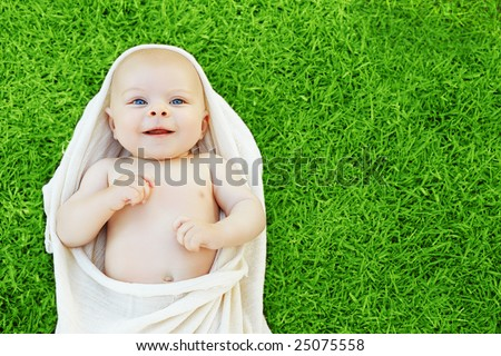 Baby boy in natural cotton cloth resting on green grass, space for text