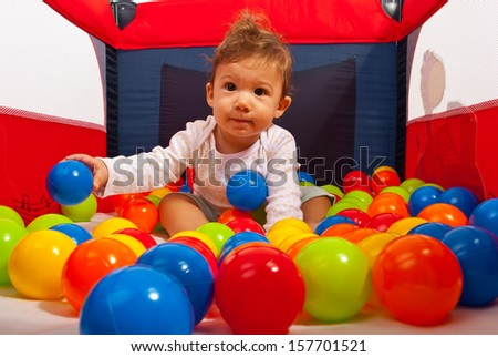 Baby boy in playpen playing with balls