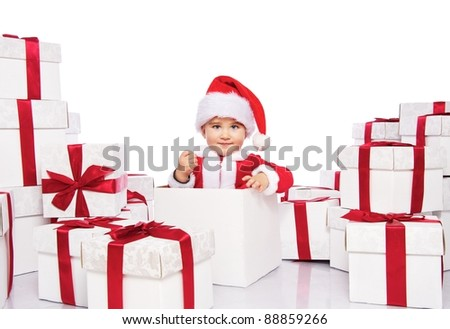 Baby boy in Santa Claus costume sitting inside gift box