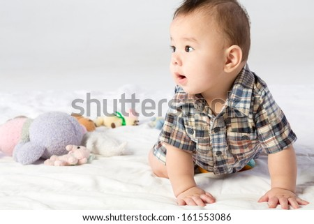 Baby boy in shirt with stuffed toys in studio