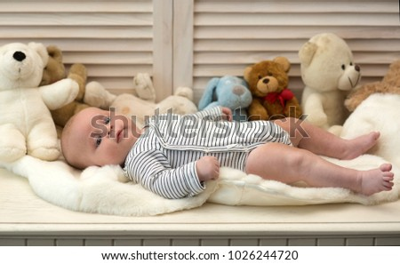 Baby boy in striped bodysuit. Baby lying on soft white duvet. Childhood and innocence concept. Infant with blue eyes and peaceful smile among teddy bears on wooden background, defocused #1026244720