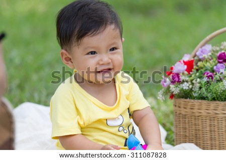 baby boy in yellow shirt sit and play toy with basket of flower in the park