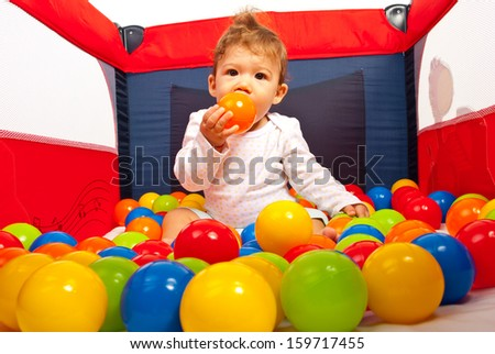 Baby boy inside playpen with colorful balls