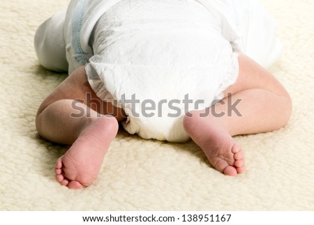 Baby boy is lying with diapers on furry blanket