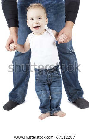 Baby boy is trying to walk with his parent.