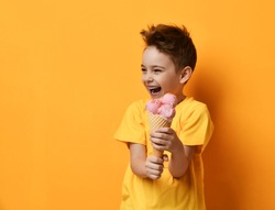Baby boy kid eating strawberry ice-cream in waffles cone happy screaming laughing on yellow background with free text copy space
