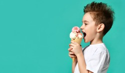 Baby boy kid hold three scoops of strawberry and vanilla ice cream in waffles cone on blue mint background with free text copy space