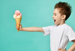 Baby boy kid hold three scoops of strawberry and vanilla ice-cream in waffles cone on blue mint background with free text copy space