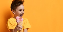 Baby boy kid in blank t-shirt with text space hold strawberry pink ice-cream in waffle cone happy laughing looking at the corner on yellow background