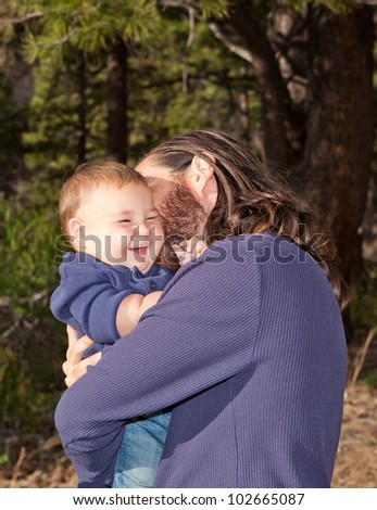 Baby boy laughing when his dad cuddles him