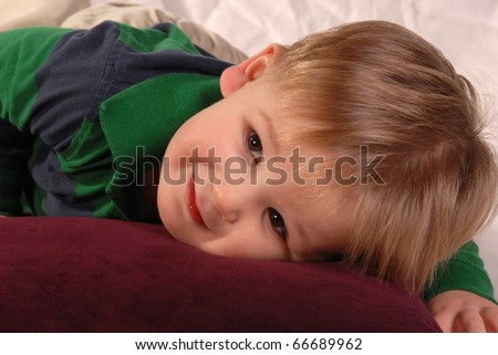 Baby boy laying on a pillow innocent look. Wearing casual cloths on white crinkled background.