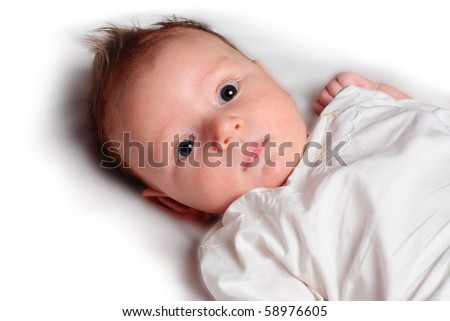 Baby boy lie on white diaper and look