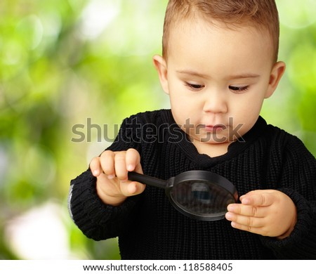 Baby Boy looking at Magnifying Glass against a nature background