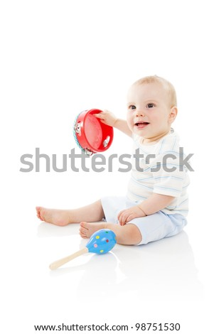 Baby boy (8 months old) shaking a tambourine, isolated on a white background.