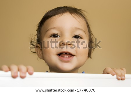 Baby boy - 11 months - smiling while reaching out of his bed holding the railing with both hands. - stock photo