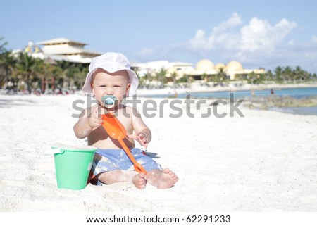 Baby boy playing in sand on a tropical beach