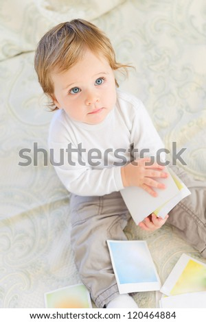Baby boy playing with color cards indoors
