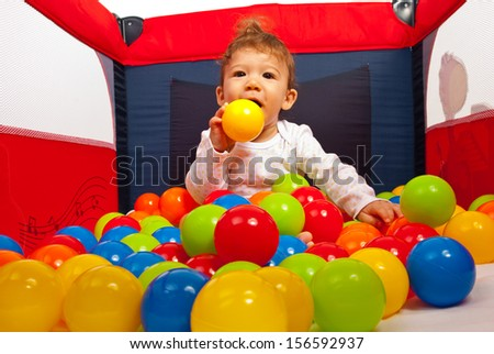 Baby boy playing with colorful balls in playpen