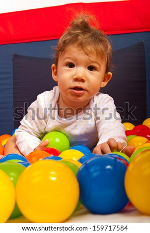 Baby boy playing with colorful ballsinside playpen