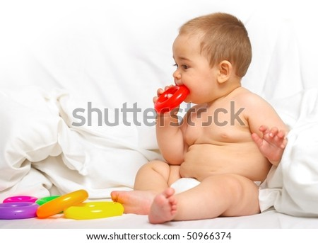 Baby boy playing with colorful toys in the bed