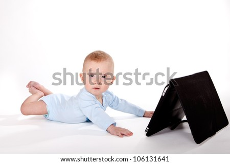Baby boy playing with computer tablet - stock photo