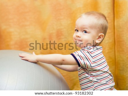 baby boy playing with fit ball in nursery