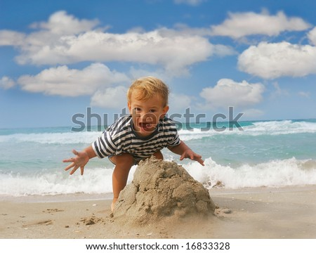 baby boy playing with sand on beach
