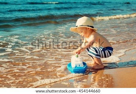 Baby boy playing with ship toy at sea. Child os on vacation in summer at the beach on vacations