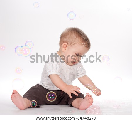 baby boy playing with soap bubbles on white background