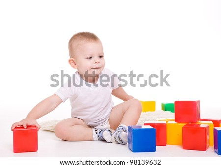 Baby boy plays with toy blocks over white background