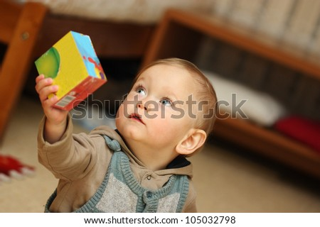 Baby Boy plays with toy in playroom