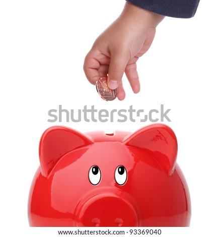 Baby boy putting coin into a piggy bank - stock photo