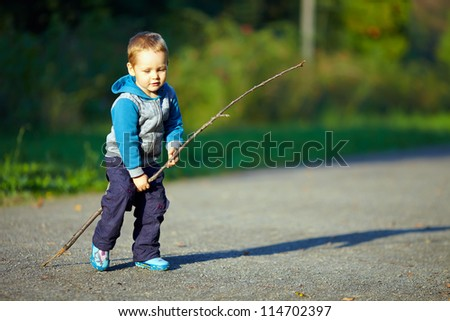 baby boy riding an imaginary horse - stock photo