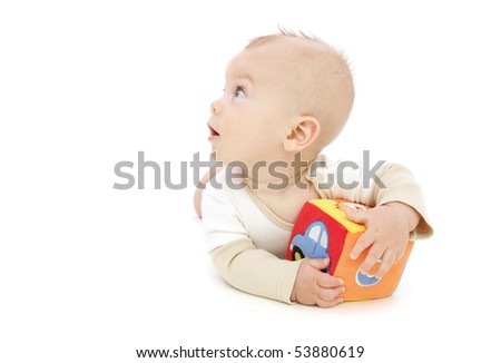 Baby boy rolling and playing with a colorful block, on white background