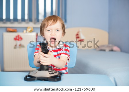 Baby boy screaming when playing computer games with joystick