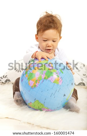 Baby boy sitting down and searching world globe