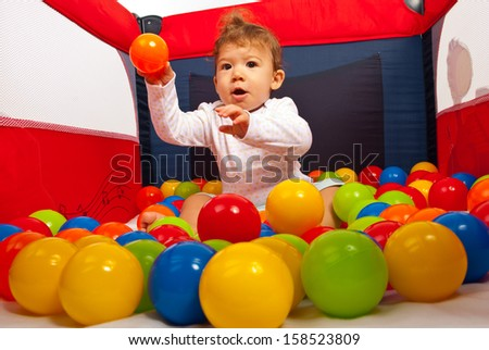 Baby boy sitting in playpen with colorful balls and throwing a orange ball