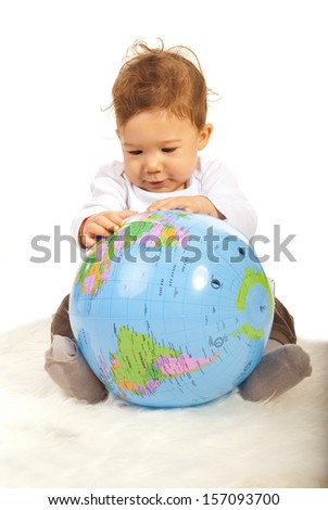 Baby boy sitting on fur blanket and searching on a world globe