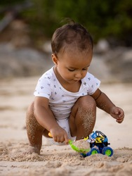 Baby boy sitting on sandy beach, playing with sand scoop and toy car. Warm sunny day. Happy childhood. Cute little boy. Summer vacation at the sea. Pandawa beach, Bali, Indonesia