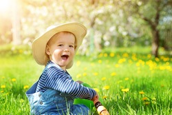 Baby boy sitting on the grass with dandelion flowers in the garden on beautiful spring day. Child in straw hat. Little gardener